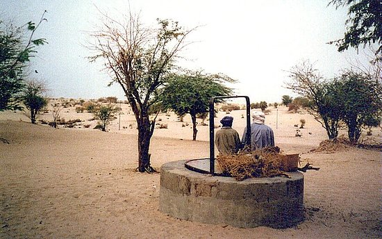 Figures sitting on a well head on the outskirts of Timbuktu looking out into the Sahara