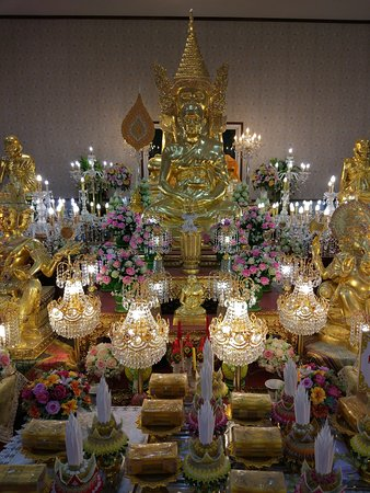 Sparkling chandeliers add glitter to the golden images inside Wat Tha Ka Rong
