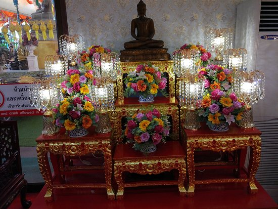 Luminous shower of droplets and flowers adorn the statue of Lord Buddha in a warm corner of Wat Tha Ka Rong