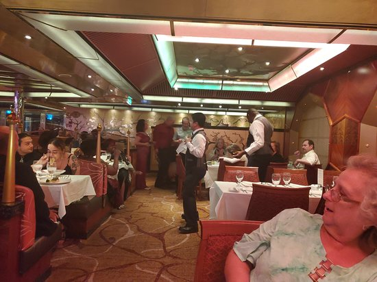 Carnival Glory: Waiters putting on a show.  Some diners danced as well and you might say more adult in nature but great fun for all!!!