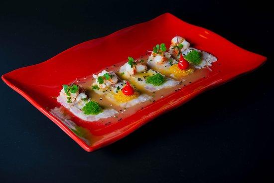 Sashimi de corvina con gambas ajillo, maiz brasa, leche de tigre, y huevas de wasabi.