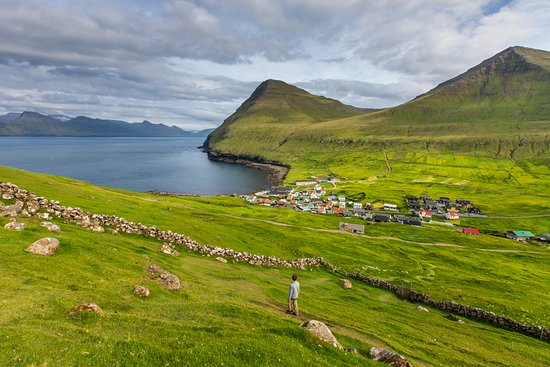 Gjogv, หมู่เกาะแฟโร: Our favorite hike in the Faroe Islands this summer? This one, above the village of Gjógv. It wasn't even in our plans, but my son and I looked out from our hotel room and saw people hiking along an upper ridge line. We grabbed water and snacks and started walking. The path went up to the left along the cliff and then ended at other cliffs. Coming down we cut through the sheep pasture that's pictured. And we liked it so much that we did it again the next day. Always fun to be spontaneous...