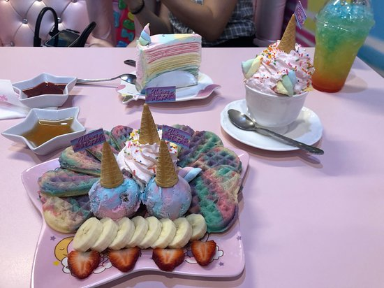 Rainbow waffles with ice cream, a hot tea (with whipped cream?!), a crepe cake and some sort of rainbow iced drink.