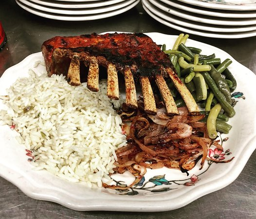 Kingston, NH: An elegant rack of lamb, pan seared, seasoned, and oven roasted with red wine sauce with  caramelized onions, rice pilaf, and freshly picked green beans.