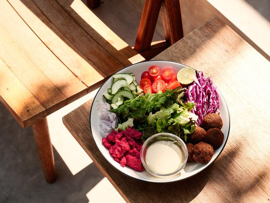 Falafel Salad (VEGAN) with mixed lettuce, cherry tomato, cucumber, shallot, beetroot hummus, falafel balls, red cabbage, lime, tahini dressing