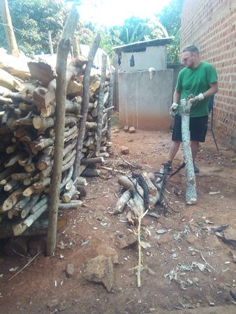 Kasangati, Уганда: Benjamin Holler a volunteer from Austria volunteering to pile firewood to be used at school. This also involved splitting the world. Thank you so much for the work well done.