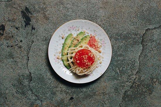 Yema curada con fideos fritos de arroz, palta y nuez