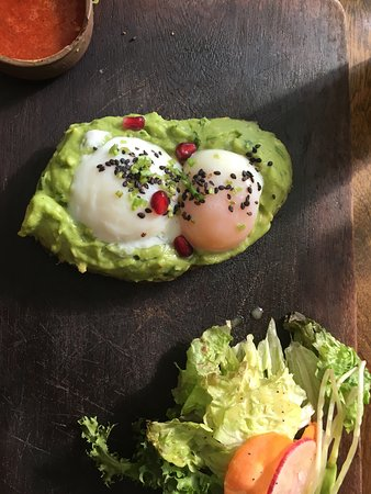 Cold running poached eggs on hot guacamole and pared with hot salad