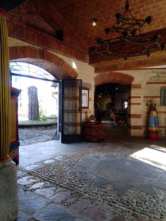 La Palma, El Salvador: The grand entrance hall, layered with sandstone to form a solar feature. Antique columns, iron pieces, hand-painted wood boards and local handcrafted pieces decorate this main room.