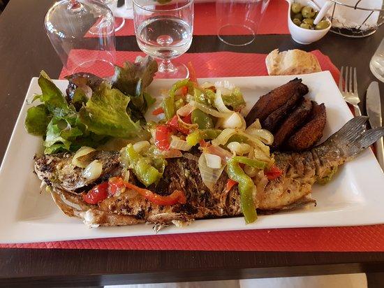 Bar cuisiné avec poivrons, oignons accompagné de riz, salade verte et bananes plantain
