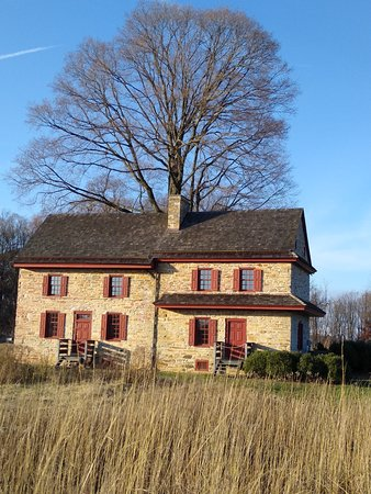 The house at the top of the hill/meadow.