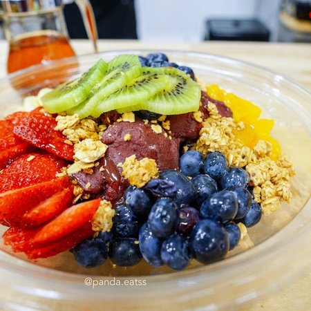 """Açaí Bowl. Not blended """"it's all açaí """", surrounded by all the fruits. Add your own honey and other toppings at no additional cost."""