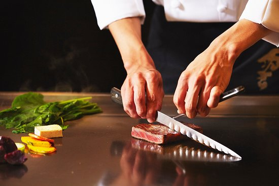 Teppanyaki with a selection of menu including beef, seafood, and assorted vegetables.