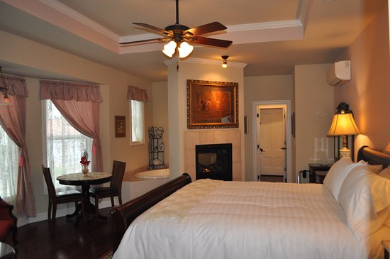 Alexander Valley Suite features a see-thru fireplace and deep soaking tub for two, king bed, refrigerator, in this grand room at the River Belle Inn.
