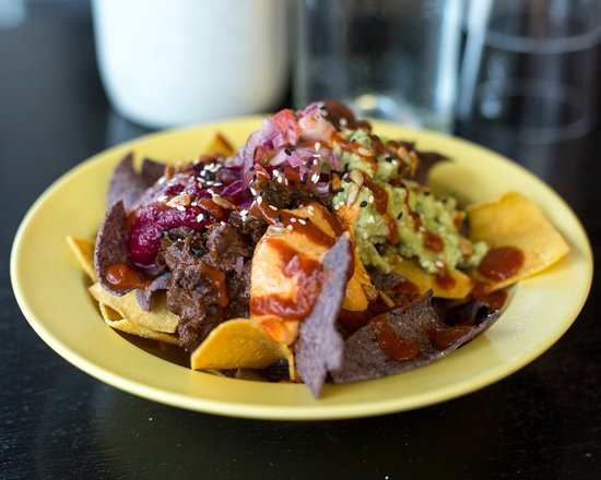 Nachitos, with a selection of dips including: Mole beans, guacamole, chipotle hummus, salsa.