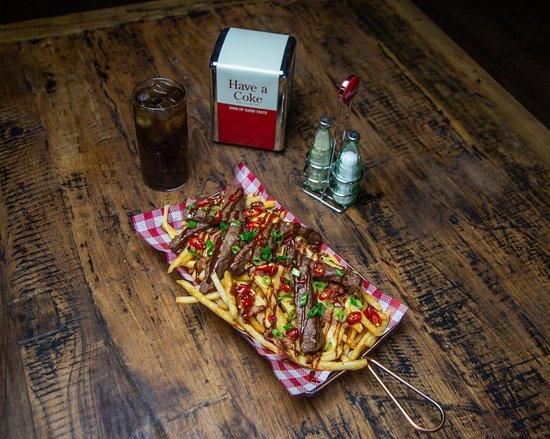 Downtown Fries: Smoky bacon, seared wagyu striploin, nacho cheese, house made BBQ sauce, onion rings