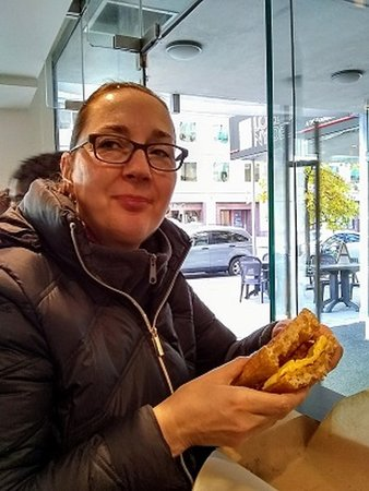 My wife eating a waffle, bacon, egg and cheese Sandwich!