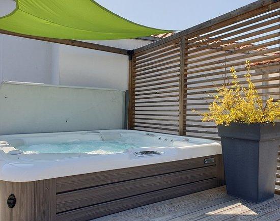 L'espace détente : un solarium aménagé à l'abri des regards et un spa bain hydromassant