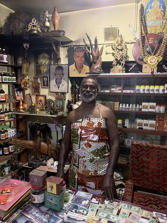 Mr Gurukkal in his store, with photos of his father and grandfather.