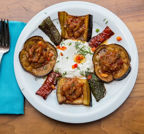 TASSHUKA Deep fried aubergines and peppers, served in a slow cooked tomato sauce with yogurt