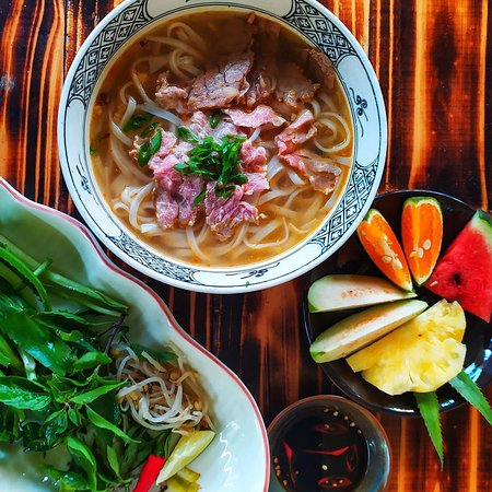 Pho Bo, a Vietnamese dish with noodles and beef. Served with herbs and tasty broth.