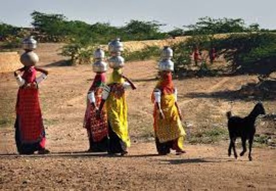 women bringing water from natural water well...