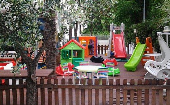 Area giochi esterna per bimbi con pavimentazione in legno, sicura e recintata.