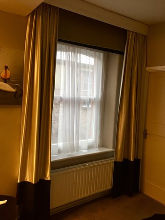 Curtains open showing radiator and sash windows