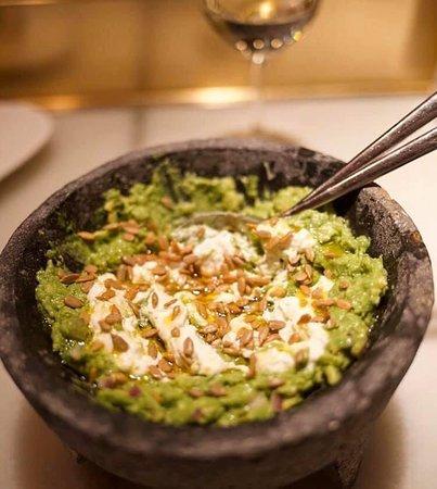 Guacamole hecho en mesa, burrata rota y pipas de girasol.