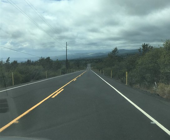 Long approach road to Naalehu and United Methodist Church.