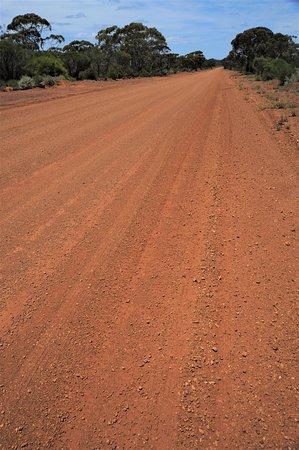 """Strada che conduce alla """"città"""" di Ora Banda, il cui pannello indica il numero di abitanti = 1 (uno) - Western Australia. Cliccare sulla foto per vederla come scattata."""