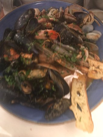 Polipo alla griglia con pure di patata viola, gnocchi, spadellata di carciofi e calamari