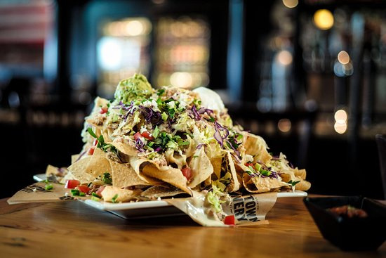 Loaded Nachosaurus Chips, white queso, jalapeños, onions, tomatoes, red cabbage, guacamole, cilantro, lettuce, queso fresco, sour cream. Your choice of spicy pulled chicken or picadillo beef