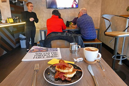 My Brunch - a Pancake/Bacon stack with Maple Syrup and a Cappuccino. (Complementary Toberone sweet). Waitress, Cheryl, in the background, to the left.
