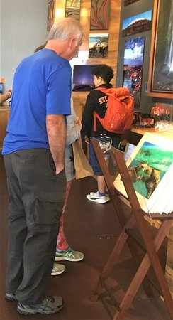 Tourist inspecting paintings at the Extreme Exposure Gallery.