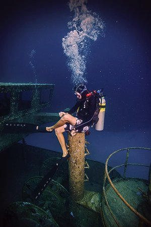 SCUBA Instructor Ragime P sits on a vent stack of the USS Kittiwake, a former United States Navy submarine rescue vessel, off Seven Mile Beach, on the West Shore of Grand Cayman Island. Purchased by the government of the Cayman Islands, the Kittiwake was intentionally sunk on January 5, 2011, to create an artificial reef in the Cayman Marine Park.