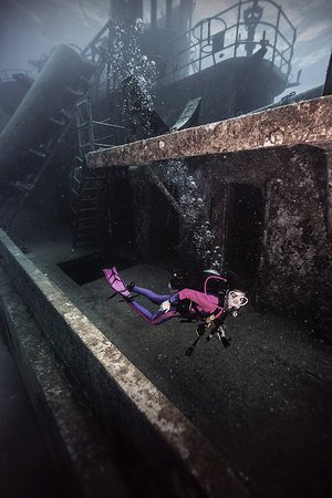 SCUBA Diver Sally H explores the wreck of the USS Kittiwake, a former United States Navy submarine rescue vessel, off Seven Mile Beach, on the West Shore of Grand Cayman Island. Purchased by the government of the Cayman Islands, the Kittiwake was intentionally sunk on January 5, 2011, to create an artificial reef in the Cayman Marine Park.