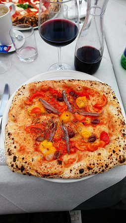 "This is the pizza ""Doppio Napoletano"" with 3 different kind of tomatoes --including those yellow ones-- anchovies and other essential herbs and sauce and cheese etc. That wine was one of the best wines I tasted along with a lunch. Very good."