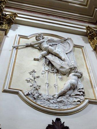 Stucco nella parete di dx: si noti lo scheletro che emerge sotto all'angelo e i teschi riprodotti sul telo sorretto dall'angelo superiore, elementi tipici nelle chiese dedicate alla Anime del Purgatorio.