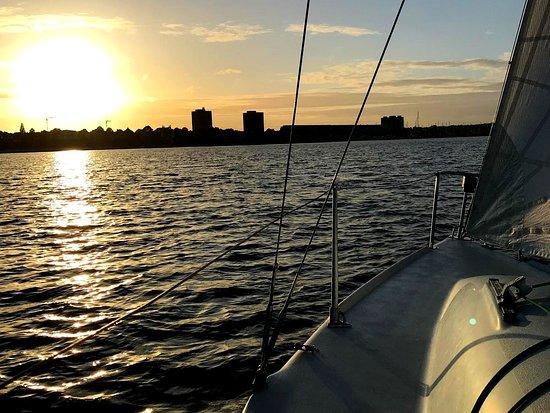 Wir segeln mitten auf der Kieler Förde vor Schilksee – während unserer Kurszeiten haben wir oft das Glück in der Abendsonne segeln zu können. Eine wunderbare Kulisse, die du ganz nebenbei genießen kannst. Segeln lernen kann dir ein bisschen Urlaubfeeling schenken. Komm an Bord, wir freuen uns auf dich! ⛵☀️