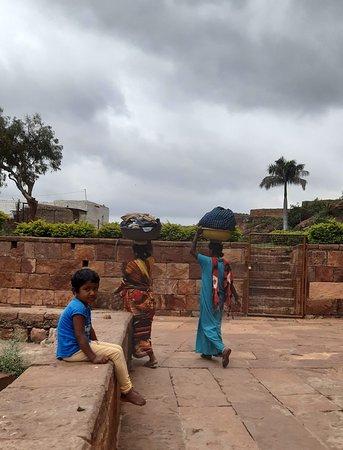 Women walking towards water tank to make laundry in Badami