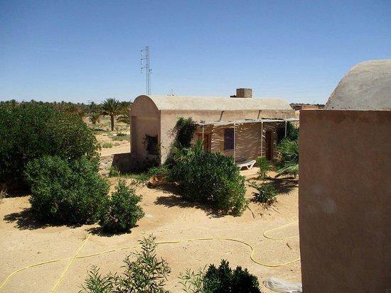 Une maison d'hôtes différente Pourquoi différente ? Parce que son emplacement à l'entrée du Sahara est unique ! Vous ouvrez portes et fenêtres et vous y êtes ! Vous pouvez voir passer des caravanes et des troupeaux de chamelles et du sable à perte de vue ! De l'autre côté, tout près, s'étend la vaste palmeraie verdoyante de Douz offrant d'agréables promenades ombragées. Cette maison n'est pas pour autant isolée. Une dizaine d'indigènes ont la leur et ce petit village du nom de Lehsey se trouve à