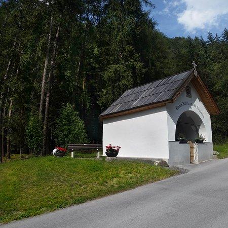Längenfeld, Österreich: Unsere Kapelle mit angelegter Grünfläche und Parkbank am Waldrand.