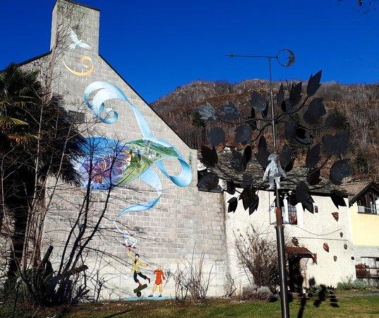 Verscio, สวิตเซอร์แลนด์: Clown Dimitri zeigt auf diesem Murales einen Balanceakt mit seinem Symboltier, dem Elefanten. Der kleine Elefant hält seinerseits ein Band in der Hand, das ein detailliertes Gemälde des Ortes des Wandgemäldes enthält.