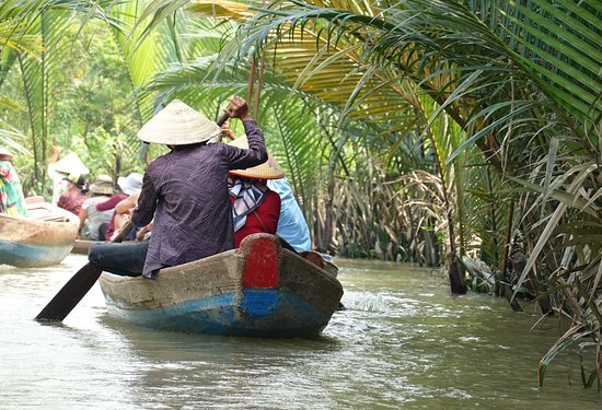 Mekong Delta, Vietnam: Very pleasant ride on old wooden boats trough one of the Delta Mekong canals shaded by coconut trees
