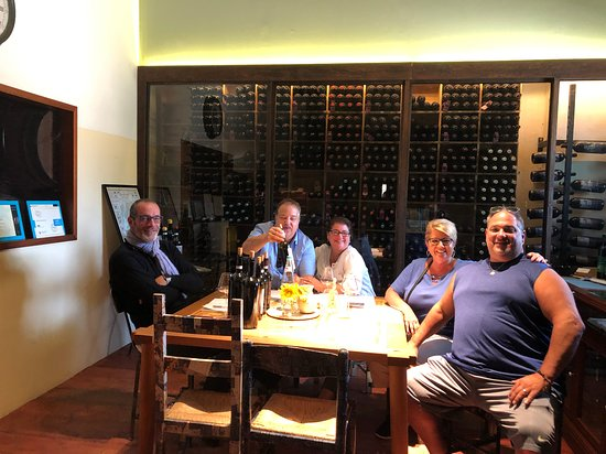Pietraia, Italy: My wife and I sitting to the right of Deni Zeni, and my wives brother and sister-in-law to the far right.  We are in the tasting room at Leuta Wines, a wonderful experience!