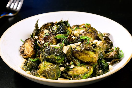 Honor: Crispy Brussels Sprouts - Savory onion caramel, lime, mint, roasted garlic, and marcona almonds.