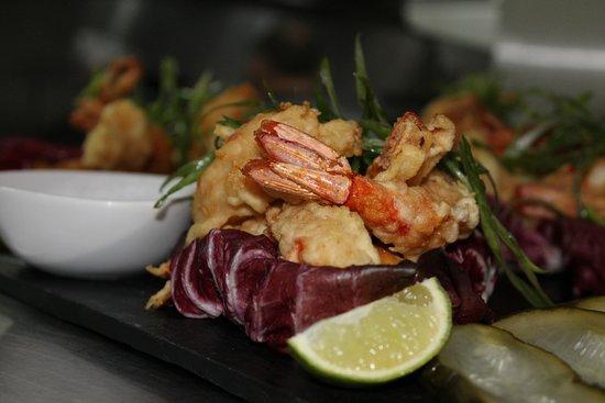 Langostinos en tempura, con pepinos encurtidos, batatas y salsa dulce picante.