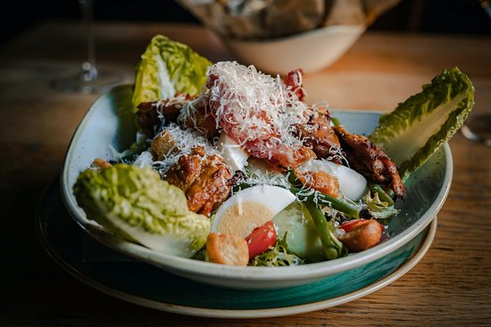 Caesarsalade: Frisse salade - Bacon - Gekookt ei - Parmezaanse kaas - Haricots verts - Kruidendressing - Croutons - Brood - Kruidenboter