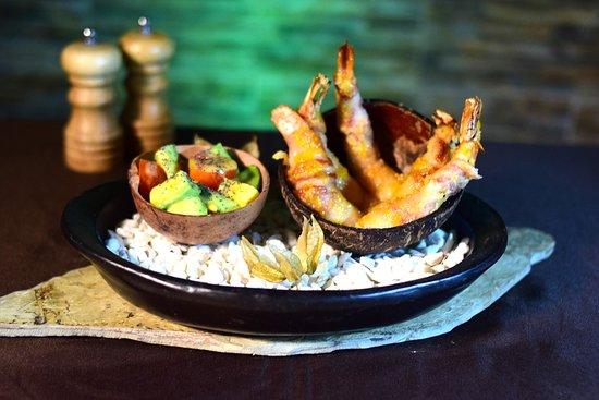 Langostinos rellenos de encocado de tollo ahumado, albardados en tocineta y maíz dulce, acompañados de ensalada de aguacate y tomates con deliciosa vinagreta de lulo y amapola.